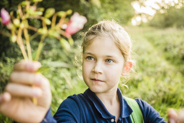 Portrait of girl holding wild flower in the nature - MOEF00567