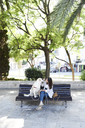 Young woman sitting on bench with her dog in the city - IGGF00316