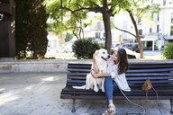 Happy young woman sitting with her dog on bench in the city - IGGF00319
