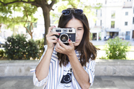 Young woman taking picture with vintage camera - IGGF00322
