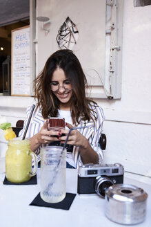 Young woman sitting in a coffee shop using smartphone - IGGF00331