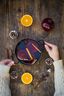 Woman's hands holding cooking pot of mulled wine with orange slices and spices - LVF06544