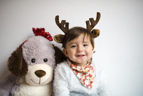 Portrait of happy baby girl with reindeer antlers headband beside her toy dog - GEMF01824