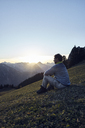 Austria, Tyrol, Rofan Mountains, hiker sitting on meadow at sunset - RBF06225