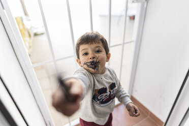 Little boy showing crayon after painting his face - JASF01848