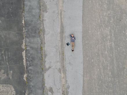 Young businessman with laptop relaxing in solitude, quadcopter view - KNSF03241