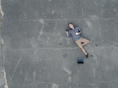 Young businessman with coffee to go lying on tarmac using mini tablet, quadcopter view - KNSF03244