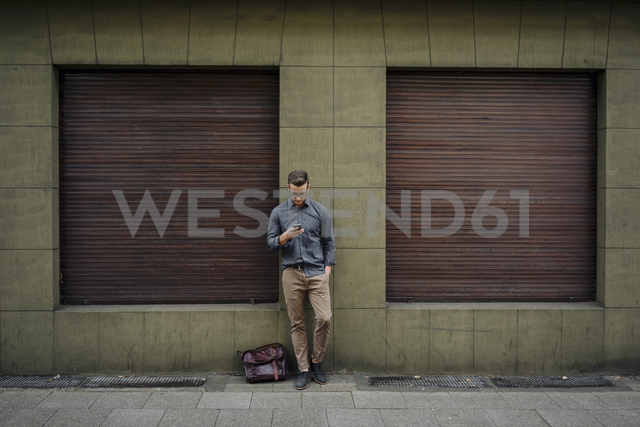 Young man leaning against house front using cell phone - KNSF03250