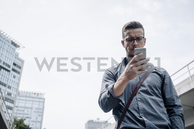 Portrait of serious young businessman looking at smartphone - KNSF03253