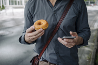 Hands of businessman holding doughnut and smartphone, Partial view - KNSF03259