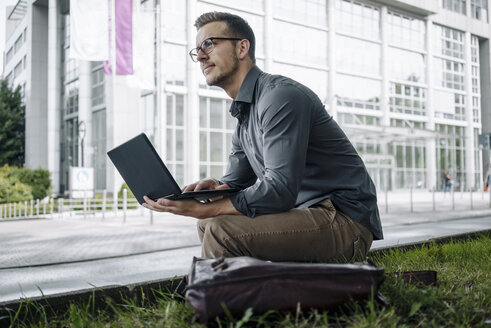 Young businessman sitting outdoors using laptop - KNSF03262