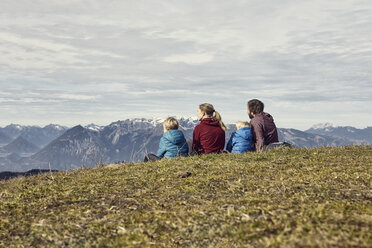 Italy, South Tyrol, Geissler group, family hiking, sitting on meadow - RBF06238