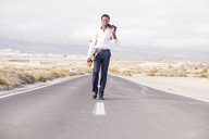 Spain, Tenerife, young businessman with skateboard walking on road - SIPF01897