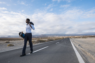 Spain, Tenerife, young businessman with skateboard walking on road - SIPF01909