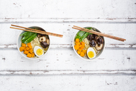 Ramen with noodles, egg, hokkaido pumpkin, mung sprout, shitake mushroom in bowl, chopsticks - LVF06551
