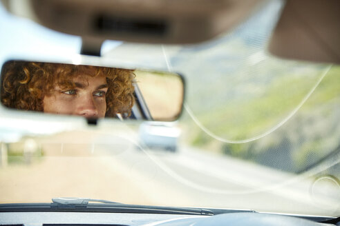 Young man driving car, rear view mirror, mirrored - SRYF00580