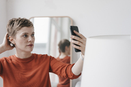 Portrait of woman holding cell phone - KNSF03264