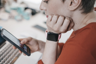 Woman wearing smartwatch using cell phone  at desk in office - KNSF03273