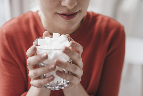 Close-up of woman holding glass full of sugar cubes - KNSF03279