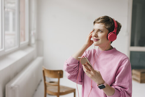 Smiling woman with cell phone and headphones listening to music - KNSF03282