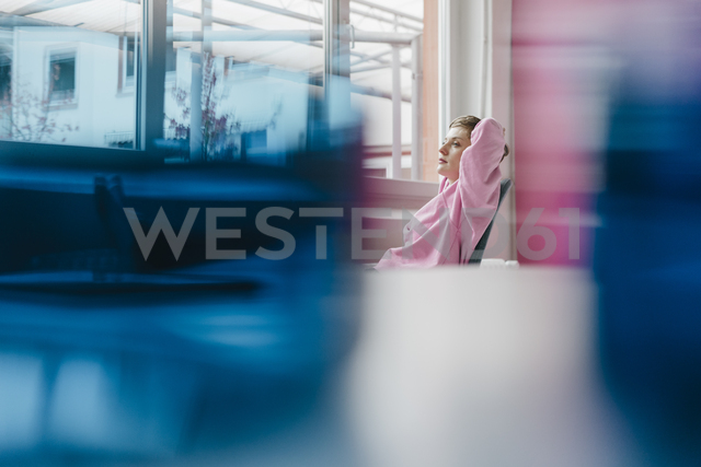 Pensive woman sitting at desk looking out of window - KNSF03285