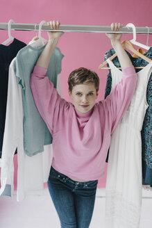 Portrait of smiling woman at clothes rail - KNSF03288