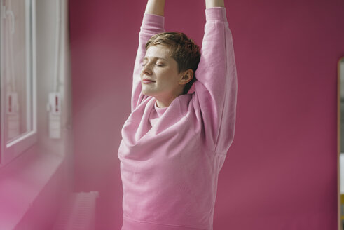 Woman in pink stretching at the window - KNSF03294