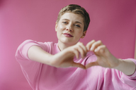 Portrait of woman in pink shaping heart with her hands - KNSF03297
