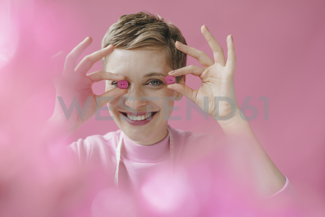 Portrait of happy tailoress holding pink buttons - KNSF03300