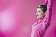 Woman in pink sportswear stretching her arms - KNSF03318