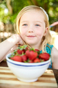 Portrait of smiling girl with bowl of stawberries - SRYF00590