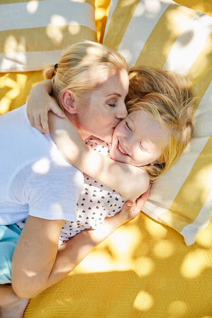 Happy girl and mother hugging and kissing on a blanket - SRYF00599 - Martina Ferrari/Westend61
