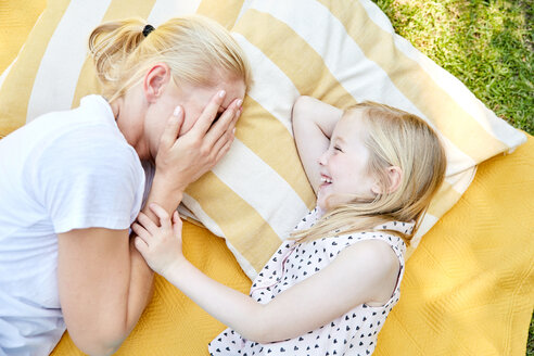 Happy girl with mother lying on a blanket - SRYF00602