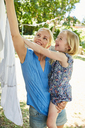 Happy girl and mother hanging the laundry on clothesline - SRYF00608