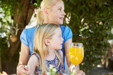 Girl with mother sitting at garden table looking sideways - SRYF00611