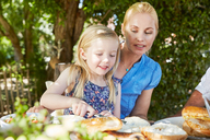Girl with mother having breakfast at garden table - SRYF00614