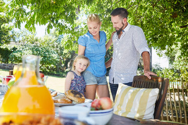 Smiling family with girl standing at garden table - SRYF00617