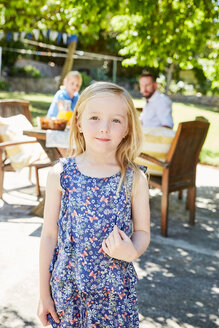 Portrait of smiling girl with parents in the background at garden table - SRYF00620