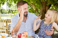 Happy girl with father sitting at garden table high fiving - SRYF00626
