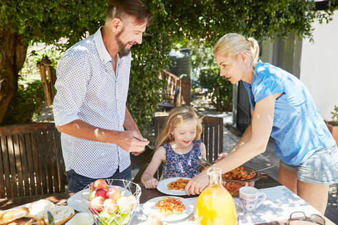 Parents dishing up pasta for daughter at garden table - SRYF00632