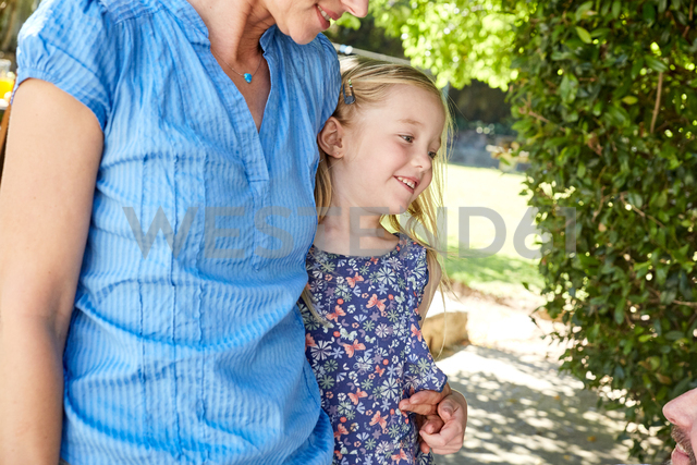 Mother embracing smiling girl outdoors - SRYF00638
