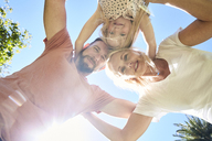 Portrait of happy family huddling under blue sky - SRYF00668