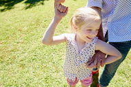 Smiling girl on father's hand in garden - SRYF00683