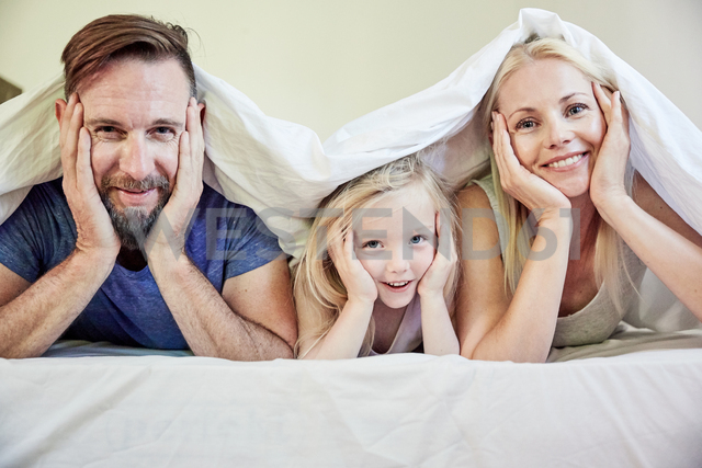 Portrait of happy family under blanket in bed - SRYF00689