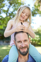Happy girl sitting on father's shoulders doing his hair - SRYF00695