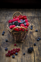 Wickerbasket of various berries on wood - LVF06564