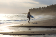 Indonesia, Bali, young surfer walking on beach - KNTF00933