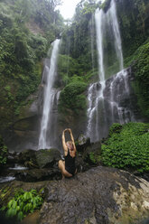 Indonesia, Bali, young woman crouching at waterfall - KNTF00936