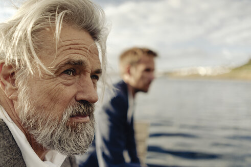 Portrait of serious senior man at a lake with man in background - KNSF03345