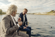 Two businessmen sitting on jetty at a lake talking - KNSF03348